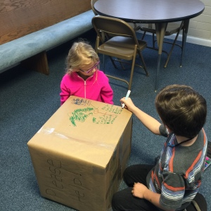 Peyton and Shane hard at work in decorating the collection boxes for winter clothing for the needy